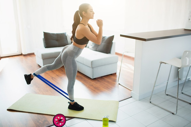 Giovane donna che fa allenamento sportivo in camera durante la quarantena. stare in piedi sul tappetino da yoga e allungare la gamba sulla schiena usando la fascia di resistenza.