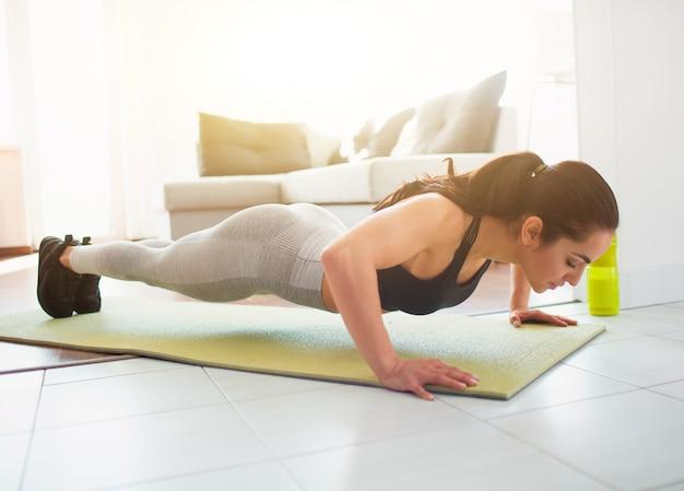Giovane donna che fa allenamento di sport nella sala durante la quarantena. forte donna potente bassa facendo push up esercizio. anche stare in posizione di plancia. fare allenamento in camera sul tappetino.