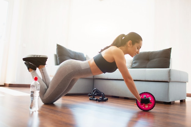Giovane donna che fa allenamento di sport nella sala durante la quarantena