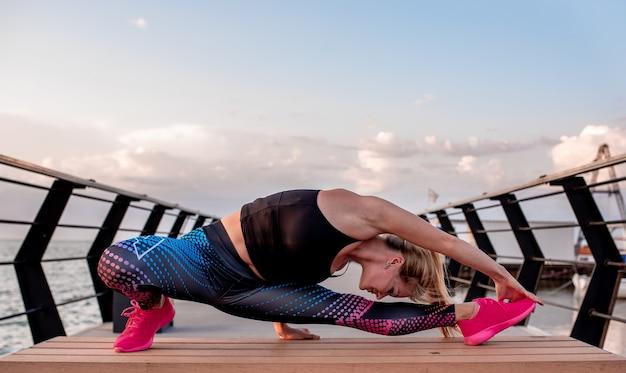 Giovane donna che fa esercizi sportivi all'alba vicino all'oceano