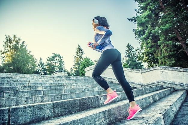 Giovane donna che fa sport e corre su per le scale.