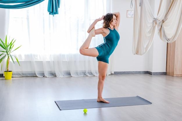 Giovane donna che fa la posa di yoga di allungamento nella classe di ginnastica