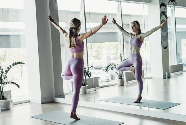 Giovane donna che fa esercizio di stretching dallo specchio sul tappetino in una luminosa classe di yoga.
