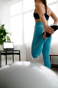Giovane donna che fa esercizio di stretching a casa, formazione in linea in forma al laptop. persona di sesso femminile in abbigliamento sportivo, allenamento sportivo internet, interno della stanza
