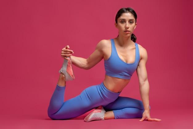 Giovane donna che fa allenamento di stretching sulla superficie marrone rossiccio