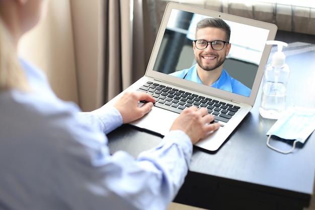 Giovane donna che fa videoconferenza con il medico sul computer portatile. coronavirus.
