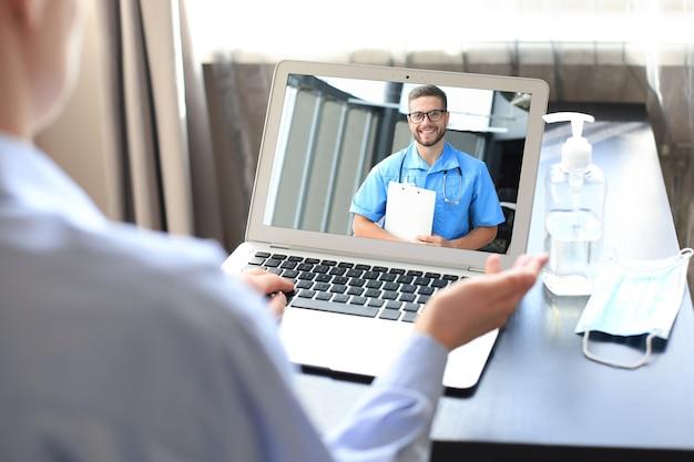 Giovane donna che fa videoconferenza con il medico sul laptop