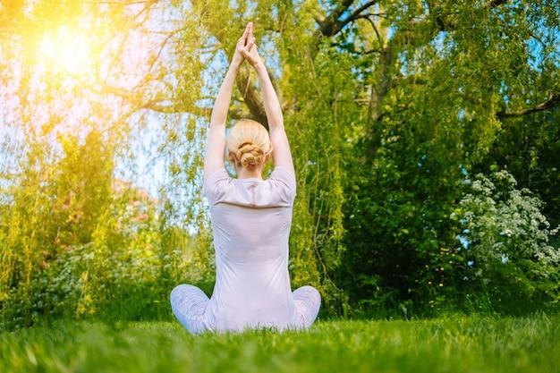 Giovane donna che fa yoga asana nel parco ragazza che allunga esercizio in posizione yoga donna felice e sana...