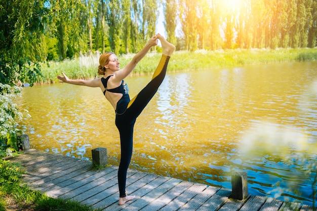 Giovane donna che fa yoga asana nel parco ragazza che si estende esercizio in posizione yoga donna felice e sana seduta nella posizione del loto e praticando la meditazione yoga e lo sport al tramonto all'aperto
