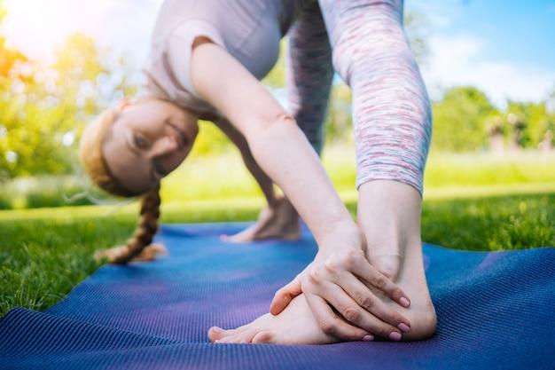 Giovane donna che fa yoga asana nel parco ragazza che si estende esercizio in posizione yoga donna sana seduta nella posizione del loto e praticando yoga meditazione sport sul tramonto all'aperto messa a fuoco selettiva