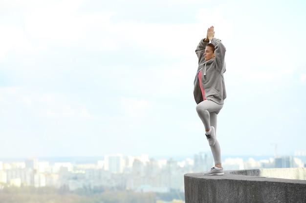 Giovane donna facendo esercizi di yoga sullo sfondo della città