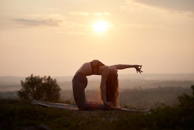 Giovane donna facendo esercizi di yoga all'aperto al tramonto