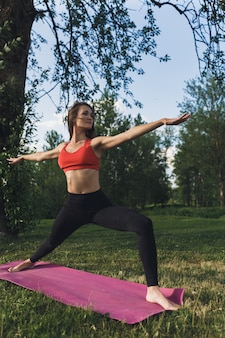 Giovane donna facendo esercizi di yoga nel parco cittadino di estate