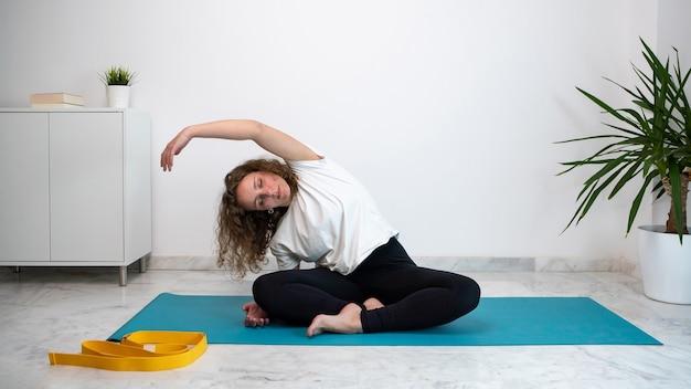 Giovane donna che fa yoga a casa durante la quarantena di coronavirus o covid 19.