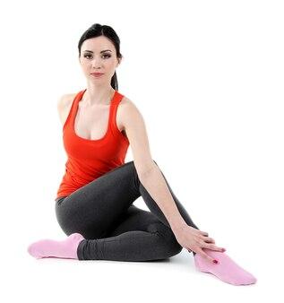 Giovane donna che fa yoga isolato su bianco