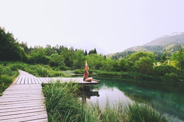 Giovane donna che fa yoga e medita nella posizione del loto sullo sfondo della natura
