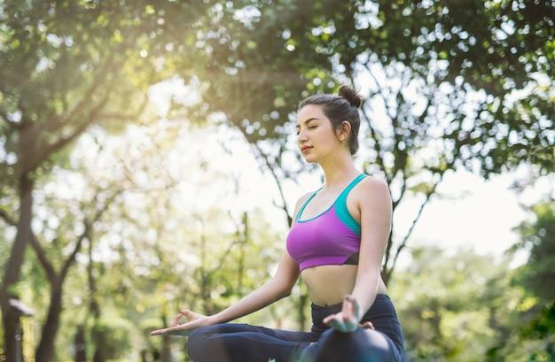 Giovane donna che fa yoga nella sosta di mattina