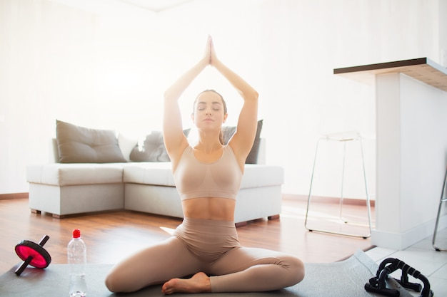 Giovane donna che fa allenamento di yoga nella sala durante la quarantena. la ragazza si siede in posizione asana con le mani insieme sopra la testa. meditare da solo nella luminosa stanza soleggiata.