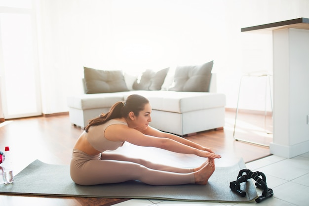 Giovane donna che fa allenamento di yoga nella sala durante la quarantena. sedersi da solo sull'uomo e sporgersi in piedi in piedi. esercizio fisico senza attrezzi da palestra.