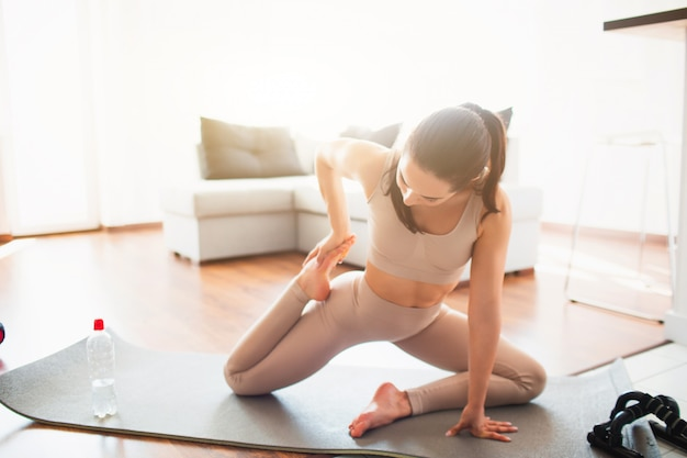 Giovane donna che fa allenamento di yoga nella sala durante la quarantena. mettiti in posa yoga con le ginocchia piegate. esercizio e allenamento a casa.
