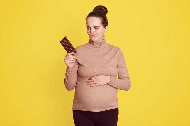 La giovane donna dubita di mangiare cioccolato o no, posa isolata su un muro giallo, tiene una barretta di cioccolato in una mano e guarda con espressione facciale dubbiosa, ha bisogno di mantenere una sana alimentazione.