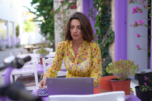 La giovane donna in un vestito in un caffè luminoso della via con un computer portatile beve caffè turco