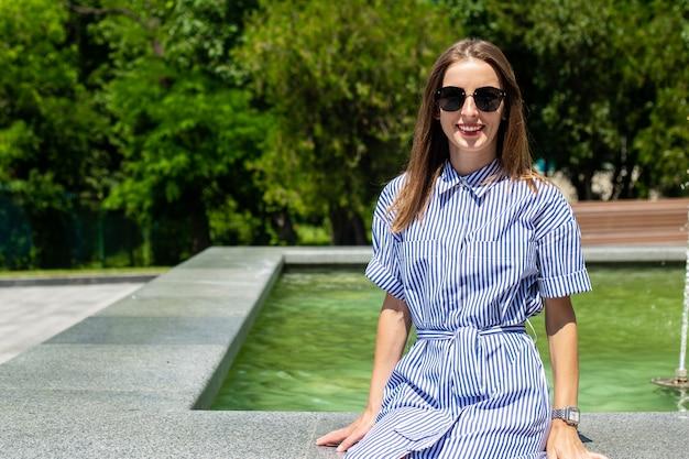 Giovane donna in abito e occhiali si siede vicino a una fontana nel parco.