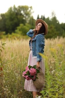 Giovane donna in abito, cappello e giacca di jeans che tiene il mazzo di fiori rosa ortensie,