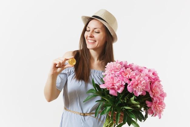 Giovane donna in abito, cappello che tiene bitcoin, moneta di colore dorato, bouquet di bellissimi fiori di peonie rosa isolati su sfondo bianco. affari, consegna, shopping online, concetto di valuta virtuale.