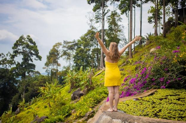 La giovane donna in un vestito allargò le braccia davanti a una foresta tropicale vista posteriore