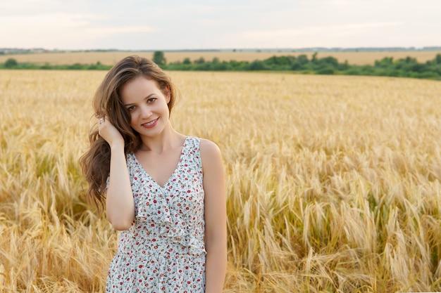 Giovane donna in abito sul campo di grano estivo. ragazza sorridente sul prato dorato. libertà