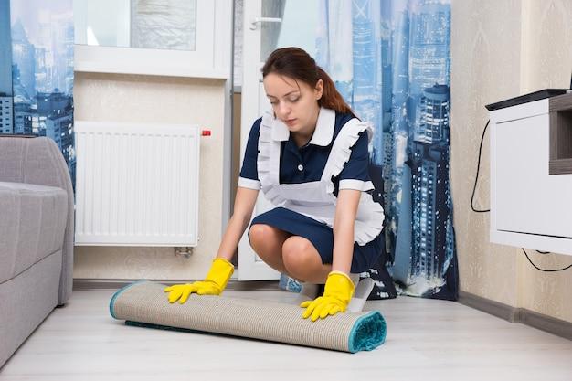 Giovane donna vestita con un'uniforme ordinata e un grembiule bianco che fa le pulizie chinandosi per arrotolare un tappetino in un soggiorno per pulire il pavimento sottostante