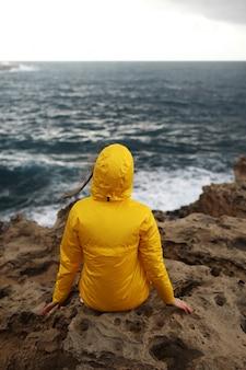 La giovane donna si è vestita in impermeabile giallo che si siede sulla scogliera che osserva sulle grandi onde del mare mentre gode del bello paesaggio del mare nel giorno piovoso sulla spiaggia rocciosa in tempo nuvoloso della primavera
