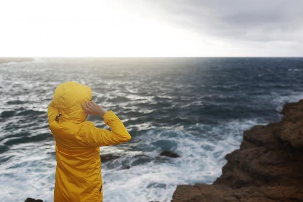 La giovane donna vestita in impermeabile giallo in piedi sulla scogliera a guardare grandi onde del mare mentre vi godete il bellissimo paesaggio marino in una giornata piovosa sulla spiaggia di roccia in tempo nuvoloso primaverile