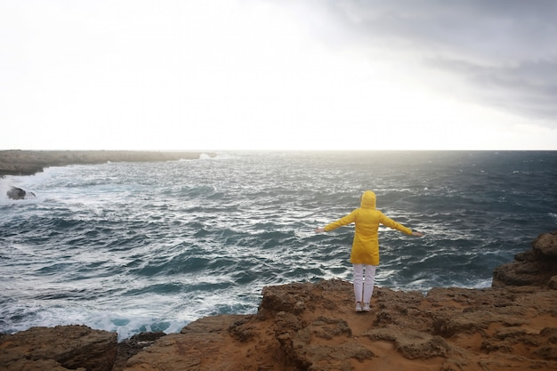 La giovane donna si è vestita in impermeabile giallo che sta con le armi stese mentre gode del bello paesaggio del mare nel giorno piovoso sulla spiaggia rocciosa in tempo nuvoloso della primavera