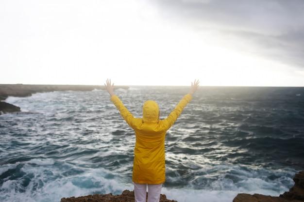 La giovane donna si è vestita in impermeabile giallo che sta con le armi stese mentre gode del bello paesaggio del mare