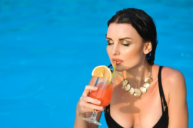 La giovane donna beve il cocktail dell'alcool con l'arancia su una piscina.