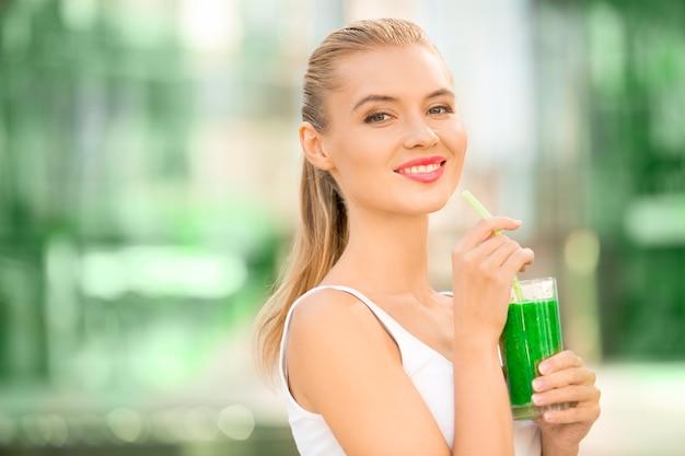 La giovane donna beve frullato sano detox all'aperto