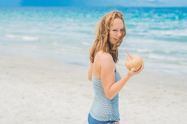 Giovane donna che beve latte di cocco sulla spiaggia