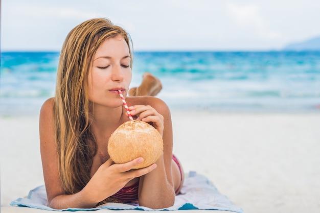 Giovane donna che beve latte di cocco sulla chaise-longue sulla spiaggia