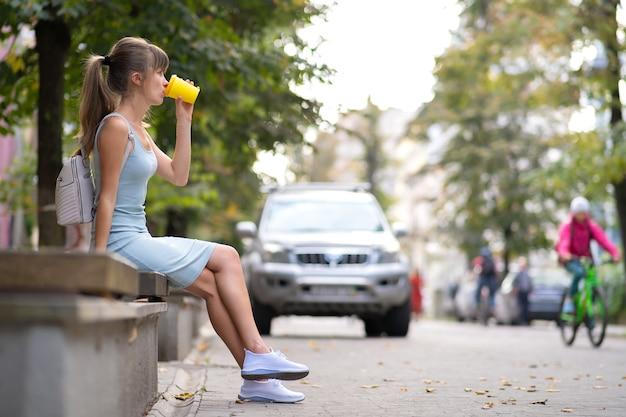 Giovane donna che beve caffè dal bicchiere di carta seduto sulla panchina della città nel parco estivo.