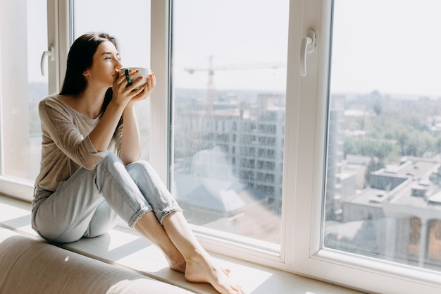 Giovane donna che beve il caffè a casa