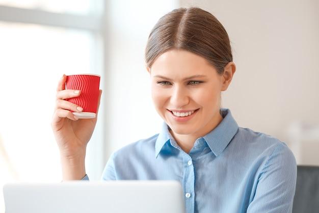 Giovane donna che beve caffè mentre lavora in ufficio