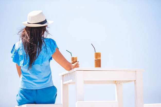 Giovane donna che beve caffè freddo godendo della vista sul mare nella caffetteria all'aperto