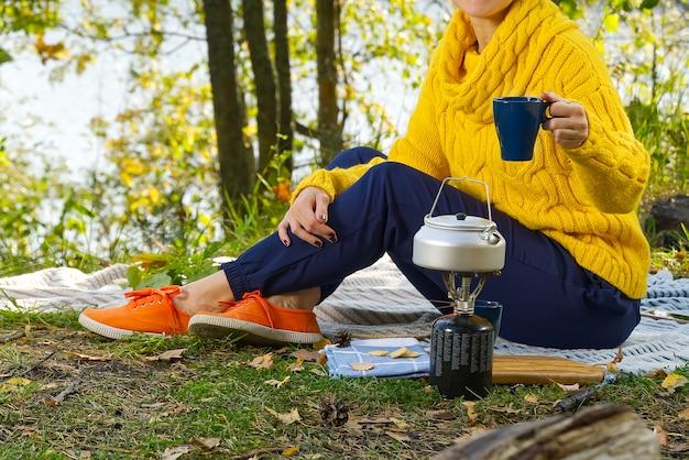 La giovane donna che la beve ha appena fatto il caffè del mattino fuori nella foresta, seduto sulla coperta