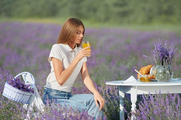 Giovane donna che beve succo in un campo di lavanda