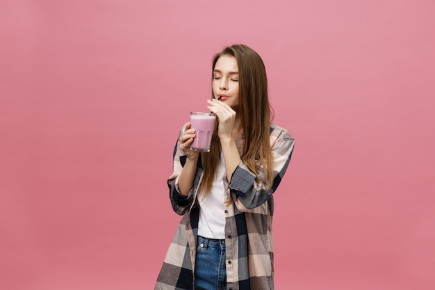 Frullato di succo bevente della giovane donna con paglia. ritratto in studio isolato.