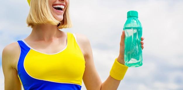 Acqua potabile della giovane donna dopo l'esecuzione. la donna in abbigliamento sportivo tiene in mano una bottiglia d'acqua. la ragazza sportiva beve l'acqua da una bottiglia su uno sfondo di cielo. concetto di stile di vita sano.