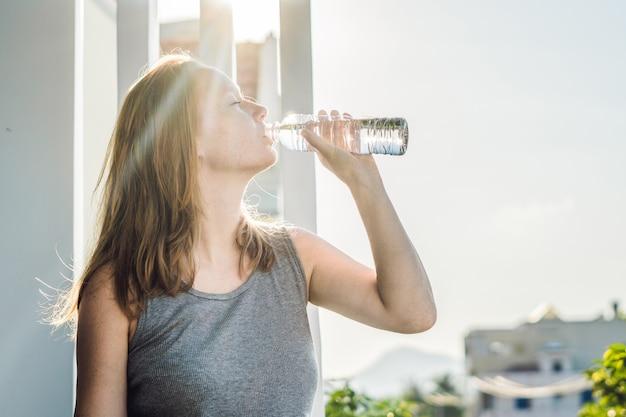 Acqua potabile della giovane donna alla luce del sole