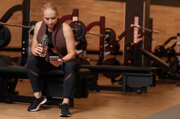 Acqua potabile della giovane donna e utilizzando il suo telefono cellulare mentre riposa dopo l'allenamento sportivo in palestra